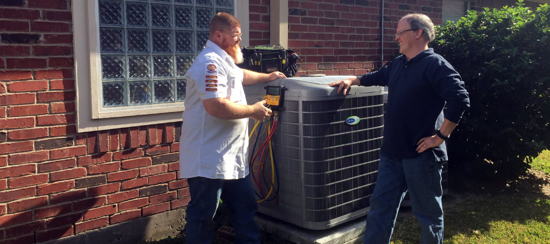Rob talking with a customer next to their outdoor condenser