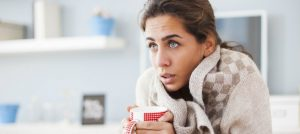 Woman feeling chilly indoors and needs a heater check