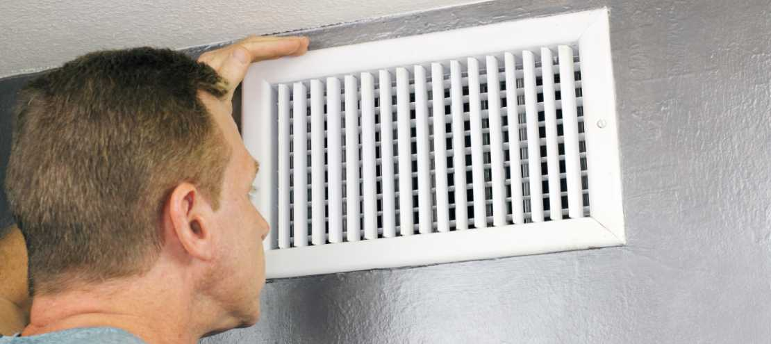 hvac technician looking at an air vent